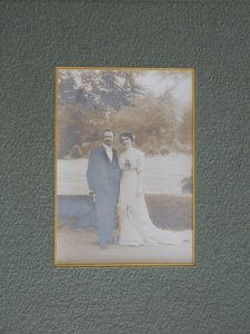A silver gelatin photograph mounted with a forest green texture window mat, with a golden rim on the opening. The photograph depicts a couple's wedding picture of a man wearing a suit and a woman wearing a white dress, they are standing in front of a lawn. The print has extensive fading, yellowing and silver mirroring.