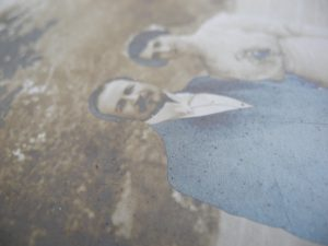 Detail of a silver gelatin photograph taken in raking light. The photograph depicts a couple's wedding picture of a man wearing a suit and a woman wearing a white dress, the picture is cropped at their waist. The print has extensive fading, yellowing and silver mirroring.
