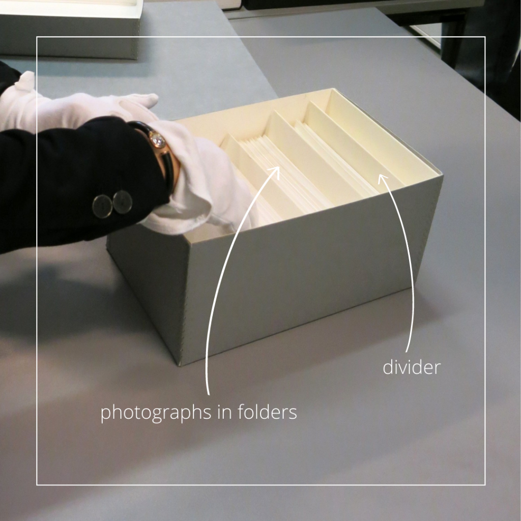 The image shows an archival box containing photographs stored in archival folders, placed vertically in the box. The folders are separated with archival matboard dividers every 5-10 cm. Hands wearing white cotton gloves are browsing in the box.
