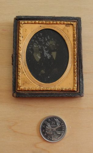 Overhead image of an ambrotype, depicting a knee-length portrait of a man and woman, mounted in a golden brass mat and preserver, in a half American style case. A Canadian quarter coin is placed along the bottom side of the photograph.