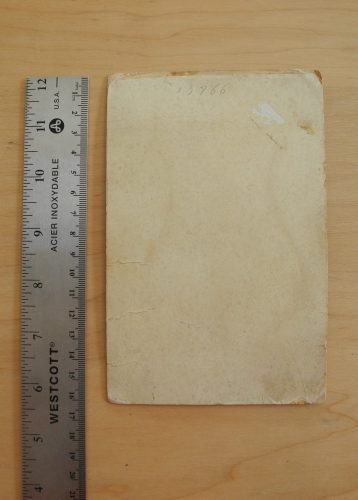 Overhead image of the back of a beige cabinet card. A metallic ruler is placed along the left side of the card.